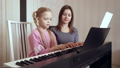 Young woman teaches little girl to play the piano. 50092121