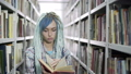 Attractive hipster female student leafing through the book while studying in library with bookshelf 50177740