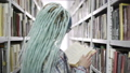 Hipster woman reading book in college library while standing near bookshelves 50177743