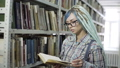 Hipster girl absorbed in reading book in library 50177776