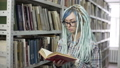 Hipster woman in library searching for a book and listing and reading it 50177780