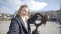 Pretty smiling blond woman in stylish look making selfie with sculpture in form of ears on street 50177781
