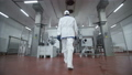 Follow footage of factory worker in cap that is walking through industrial facilities in meat plant 50177793