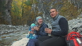 Rest and drink hot water near the mountain river. Family travels. People environment by mountains 50316821