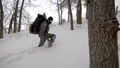 Group of four friends with big backpacks hiking in winter together, team going uphill. 50335454