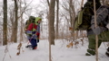 Team of four hikers walking through deep thick snow with big packs of equipment in winter forest. 50335455
