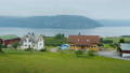 Ride along the shore of the fjord, from the window of a car you can see old houses and the 50352369