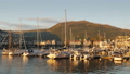 A number of small yachts are moored in a picturesque place in the background of the mountain. The 50356915