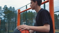 Teen listens to music on the basketball court. 50428697