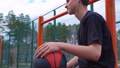 Teen listens to music on the basketball court. 50428701