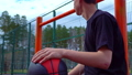 Teen listens to music on the basketball court. 50428703