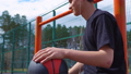 Teen listens to music on the basketball court. 50428707