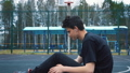 Teen listens to music on the basketball court. 50428710