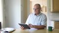 Happy Senior Man Using Digital Tablet Near The Window 50434095