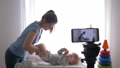 maternal care, famous blogger mum changes clothes of infant boy while recording video lesson on cell 50490725