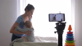 baby care, happy blogger mama changes clothes of child boy while recording training video on mobile 50490780