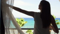 Woman on vacation open curtains and go out onto balcony to enjoy Mediterranean sea view from terrace 50509408