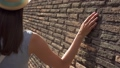 Woman slide hand against old red brick wall in slow motion. Female hand touch rough surface of stone 50509409
