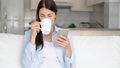 Young woman hold coffee cup and use smartphone. Female housewife browse on mobile phone chat online 50509413