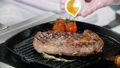 Restaurant kitchen. Chef frying piece of steak in the pan. Adding a juice on top 50537090