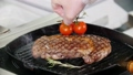 Restaurant kitchen. Chef frying piece of steak and put cherry tomatoes in the pan 50537092