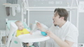Father feeding baby sitting on high chair at home 50580565