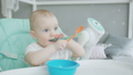 Portrait of baby sitting on highchair with spoon 50580608
