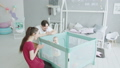 Parents having fun with baby standing in playpen 50580612
