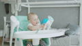 Cute baby girl sitting on highchair licking plate 50580618