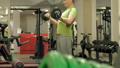 A overweight man lifts an ez barbell while standing at the gym. Exercise for biceps. Fitness 50582920