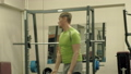 A overweight man lifts an ez barbell while standing at the gym. Exercise for biceps. Fitness 50582922