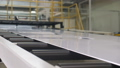 white long metal detail transported by conveyor belt closeup 50642997