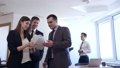 Businessmen with female colleague stands with documents in office. 50662363