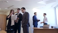 Businessmen with female colleague stands with documents in office. 50662365