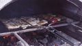 Meat and vegetables on barbeque grill in brick oven. 50667025