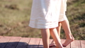 Two twin girls in linen dresses are barefoot on a wooden bridge over a stream on a summer day 50667122