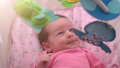 Cute newborn baby girl watching a colorful mobile toy 50773124