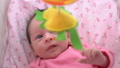 Cute newborn baby girl watching a colorful mobile toy 50773135