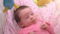 Cute newborn baby girl watching a colorful mobile toy 50773136