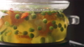 Glass pot with boiling vegetable soup on stove, with foam and bubbles. Side view. 50804888