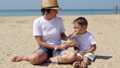 Mom feeds her child with burgers on the sandy seashore 50866799