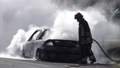 Firefighters extinguish a burning car on the road 50958056