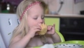 Little child girl eating a cupcake in the kitchen, slow motion. 51017673