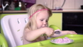 Little baby girl eating with a spoon at the children's table. 51017903