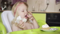 Little baby girl eating at the children's table. 51017998