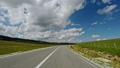 Camera moving over asphalt road trough green field against cloudy sky on sunny day in Montenegro 51333756