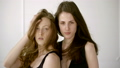 A pair of gorgeous women posing with the wind in their hair on a white background. Two girls natural 51604626