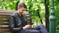 Attractive guy using a smartphone while sitting on a bench in the park 51707883