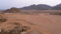 Column of a Quad Bike Rides through the Desert in Egypt on backdrop of Mountains. Driving ATVs. 51799507