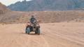 Girl on a Quad Bike Rides through the Desert of Egypt 51803564